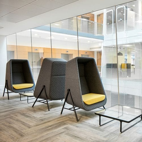 Muse high back acoustic seating in grey with yellow seat, glass coffee table collaborative and reception spaces