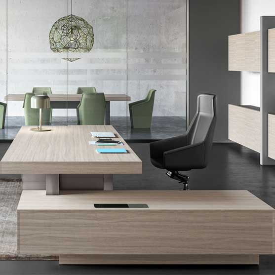 Jera Executive Desk shown in an office with executive chair and a meeting table